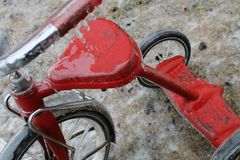Rustic Red Tricycle Covered in Ice - Closeup stock photo