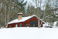Rustic red wooden barn in snow stock images