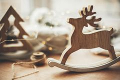 Rustic reindeer christmas toy on wooden table on background of l. Ights, wooden tree, twine, gift in linen with green branch, pine cones. Merry Christmas. Space royalty free stock image