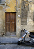 Rustic residence in Italy. Scooter waiting outside the wooden door of a residence in Florence, Italy royalty free stock images