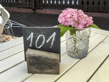 Rustic restaurant table with single hydrangea Royalty Free Stock Photo