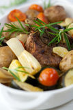 Rustic roast pork with vegetables. Roast pork with baked vegetables flavoured with rosemary stock photography