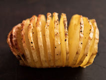 Rustic roasted hasselback potato gratin. Close up of rustic roasted hasselback potato gratin Royalty Free Stock Images