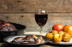 Rustic, romantic dinner - goose baked with apples and potatoes, next to a glass of red wine on a wooden background, rustic table royalty free stock photography
