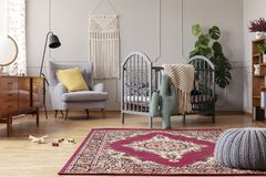 Baby bedroom with vintage furniture, real photo with copy space. Rustic rug in stylish baby bedroom with grey and vintage furniture, real photo with copy space royalty free stock photos