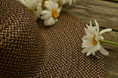 Rustic rural outdoor rough hewn table, garden hat, Daisies. A rustic rural scene of a woven straw garden hat, cut Daisies on an outdoor rough-hewn wood table Royalty Free Stock Images