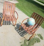 Rustic. Rusty chairs.  Globe.  Concrete green grass Royalty Free Stock Images