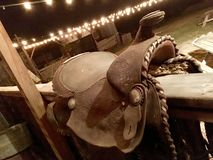 Rustic saddle over a railing. A rustic saddle over a railing on a ranch porch with country lights in the background Royalty Free Stock Image