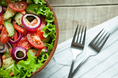 Rustic salad of fresh tomatoes, cucumbers, red onions and lettuce, dressed with olive oil and ground pepper in a wooden bowl. Top. View Royalty Free Stock Photography