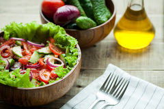 Rustic salad of fresh tomatoes, cucumbers, red onions and lettuce, dressed with olive oil and ground pepper in a wooden bowl. Top. View Stock Image