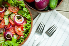 Rustic salad of fresh tomatoes, cucumbers, red onions and lettuce, dressed with olive oil and ground pepper in a wooden bowl. Top. View Royalty Free Stock Image