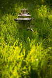 Rustic samovar on the fresh summer lawn. Copyspace.  Royalty Free Stock Photography