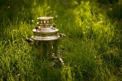Rustic samovar on the fresh summer lawn. Copyspace Stock Photos