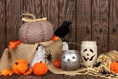 Rustic shabby chic Halloween decor scene. Rustic shabby chic Halloween decor against an aged wood background stock photo