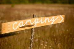 A rustic sign points to a camping area in a dry field. A rustic sign points to a camping area in a dry yellow grass field on a bright summer day Stock Image