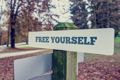 Rustic signboard outdoors in an autumn park with words Free your Stock Image