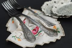 Rustic silver spoons collection on embroidery napkin on dark background. Rustic silver spoons collection on embroidery napkin royalty free stock photos