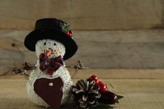Primitive snowman and pine cone on wood background royalty free stock photography