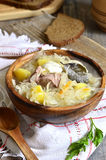 Rustic sour cabbage soup with goose in a wooden bowl. Royalty Free Stock Images
