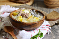 Rustic sour cabbage soup with goose in a wooden bowl. Royalty Free Stock Photography