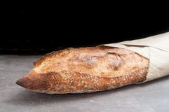 Rustic sourdough baguette served wrapped in paper on a grey slat Stock Photos
