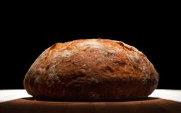 Rustic Sourdough Bread. Homemade sourdough bread on a wooden cutting board. Lit top down with warm light Royalty Free Stock Images