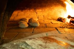 Rustic bread baking in pizza oven royalty free stock photography