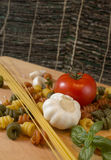 Rustic spaghetti and pasta composition. Pasta with a tomato, garlic, basil and some salt Royalty Free Stock Image