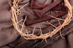 Rustic Spikes and a Crown of Thorns. A crown of thorns and rusty spikes with a rustic aged timber on a brown woven cloth. Used in the Crucifixion of Jesus in Stock Photo