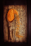 Rustic  spoon with dry red lentil on old dark wooden background Royalty Free Stock Photos