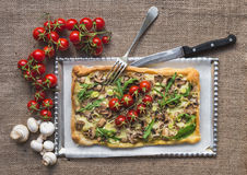 Rustic square mushroom pizza with fresh arugula and cherry-tomat Royalty Free Stock Photography
