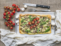 Rustic square mushroom pizza with fresh arugula and cherry-tomat Stock Image
