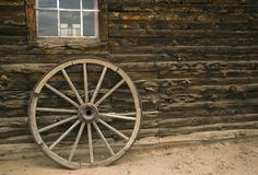 Rustic steel rimmed wooden wagon wheel against log cabin background Royalty Free Stock Photo