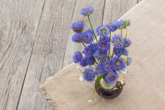 Rustic still life with a bouquet of blue flowers on a wooden bac Stock Photos
