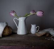 Rustic still life. bouquet of tulips, fresh bread, milk on a wooden table. black background Royalty Free Stock Photos
