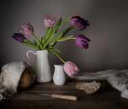 Rustic still life. bouquet of tulips, fresh bread, milk on a wooden table. black background Royalty Free Stock Photography