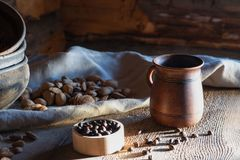 Rustic still life. ceramic mug with hot coffee. coffee beans and almond nut on a table in the sun. Still life in a village hut on the background of logs. Morning stock photography