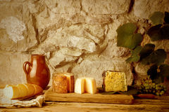 Rustic still life, cheese varieties, bread and wine Royalty Free Stock Image