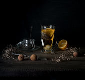 Rustic still life. cup of tea, lemon and quail eggs on a wooden table. black background Royalty Free Stock Photo