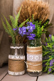 Rustic still life: dried flowers bunch and vases on vintage wooden background. Stock Photography