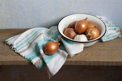 Rustic still life with onion and garlic in old fashioned bowl Stock Images