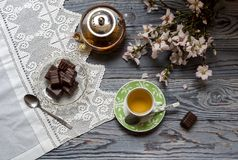 Useful, hot herbal tea, candy and flowering almond twigs. Rustic still life. Useful, hot herbal tea, candy and flowering almond twigs on a wooden table close-upn Stock Images