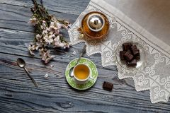 Useful, hot herbal tea, candy and flowering almond twigs. Rustic still life. Useful, hot herbal tea, candy and flowering almond twigs on a wooden table close-upn Stock Photography