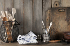 Rustic still life. Vintage rustic kitchen still life: silver glass holder with cutlery, wire basket with wood spoons, ceramic dishware, towels and cutting boards Stock Image