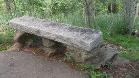 Rustic stone bench. In national park. Concrete cement  garden stock photo