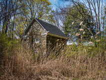 Rustic stone cabin in meadow Royalty Free Stock Image