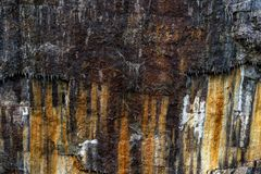 Rustic stone quarry with heavy rust patterns, cracks and icicles - high quality texture / background stock photography