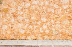 Rustic stone wall background scene with sidewalk. Rustic old natural stone wall background texture with pavement and copy space stock images
