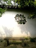 Rustic stone window in ancient Chinese garden. A photograph showing the details of a quaint antique style window on the old stone wall of a beautiful garden in royalty free stock photos