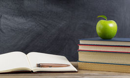 Rustic student desktop with green apple and study materials Royalty Free Stock Images